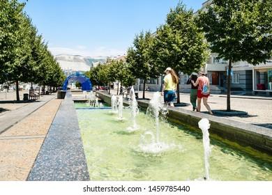 NOVOROSSIYSK, RUSSIA - JULY 7, 2019: tourists near fountain on street of the Novorossiysk Republic with obelisk. Novorossiysk is city in Krasnodar Krai, Russia, it is main country's port on Black Sea
