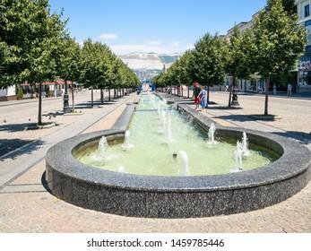 NOVOROSSIYSK, RUSSIA - JULY 7, 2019: people near fountain on street of the Novorossiysk Republic with obelisk. Novorossiysk is city in Krasnodar Krai, Russia, it is main country's port on Black Sea