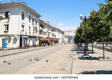 NOVOROSSIYSK, RUSSIA - JULY 7, 2019: people near old apartment houses on street of the Novorossiysk Republic. Novorossiysk is city in Krasnodar Krai, Russia, it is main country's port on Black Sea