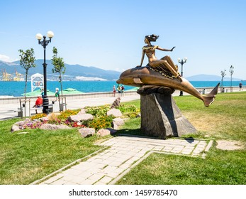 NOVOROSSIYSK, RUSSIA - JULY 7, 2019: people walk at Admiral Serebryakov Embankment near statue Girl on Dolphin. Novorossiysk is city in Krasnodar Krai, Russia, it is main country's port on Black Sea