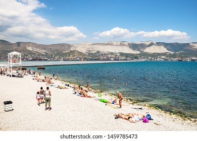 NOVOROSSIYSK, RUSSIA - JULY 7, 2019: tourists on city beach along Admiral Serebryakov Embankment in Novorossiysk city. Novorossiysk is city in Krasnodar Krai, Russia, it is country's port on Black Sea