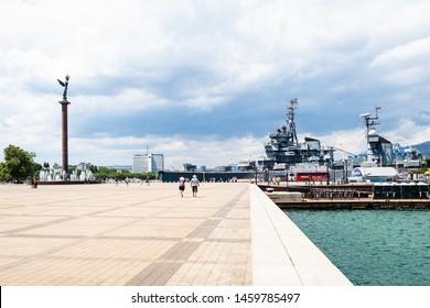 NOVOROSSIYSK, RUSSIA - JULY 7, 2019: tourists on Forum Square of Admiral Serebryakov Embankment in sea port near memorial ship cruiser Mikhail Kutuzov Novorossiysk city