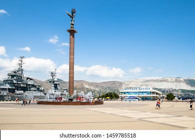 NOVOROSSIYSK, RUSSIA - JULY 7, 2019: tourists near Stele Sea Glory of Russia on Forum Square and museum ship cruiser Mikhail Kutuzov in sea port on Admiral Serebryakov Embankment in Novorossiysk city