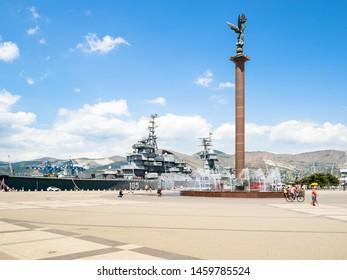 NOVOROSSIYSK, RUSSIA - JULY 7, 2019: visitors near fountain Stele Sea Glory of Russia on Forum Square and museum ship cruiser Mikhail Kutuzov on Admiral Serebryakov Embankment in Novorossiysk city