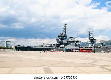 NOVOROSSIYSK, RUSSIA - JULY 7, 2019: people and excursion buses near memorial ship cruiser Mikhail Kutuzov in sea port of Novorossiysk city on Admiral Serebryakov Embankment