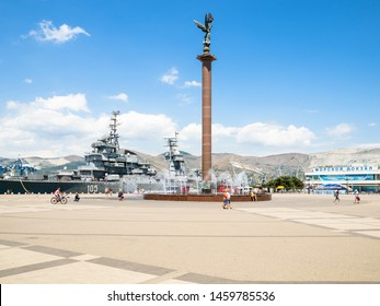 NOVOROSSIYSK, RUSSIA - JULY 7, 2019: people near Stele Sea Glory of Russia on Forum Square and memorial ship cruiser Mikhail Kutuzov in sea port on Admiral Serebryakov Embankment in Novorossiysk city