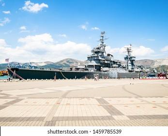 NOVOROSSIYSK, RUSSIA - JULY 7, 2019: visitors go to memorial ship cruiser Mikhail Kutuzov in Novorossiysk. Novorossiysk is city in Krasnodar Krai, Russia, it is main country's port on Black Sea