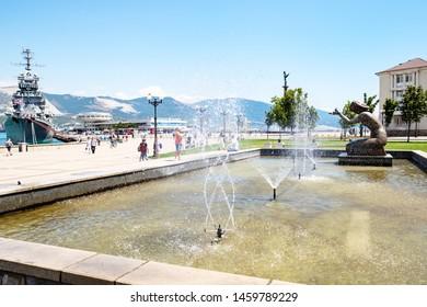 NOVOROSSIYSK, RUSSIA - JULY 7, 2019: tourists near fountain Giving Water in sea port of Novorossiysk . Novorossiysk is city in Krasnodar Krai, Russia, it is main country's port on Black Sea