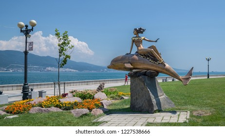 Novorossiysk, Russia - July 9: Woman and dolphin's sculpture in Novorossiysk on July 9, 2018 in Novorossiysk, Russia.