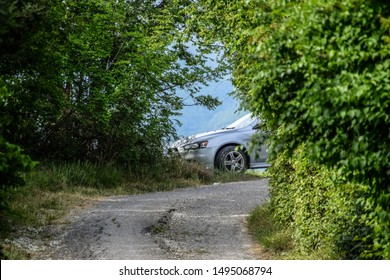 Novorossiysk, Russia - May 20, 2018: Mitsubishi Lancer 10 generation car peeks out from behind the bushes at the end of the track.