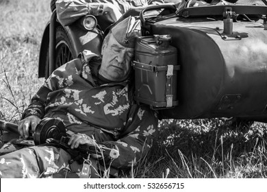 """NOVOSIBIRSK - 13 of JUNE 2015:Military-historical festival """"Siberian fire"""". Russian soldier with a gun sleeps about motorcycle"""