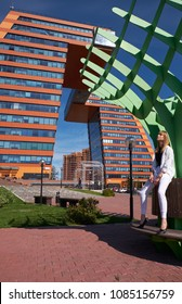 NOVOSIBIRSK AKADEMGORODOK, RUSSIA - SEPTEMBER 03, 2017: Modern young woman in white clothes near Building of Information Technology Center in Akademgorodok. The symbol of Novosibirsk technopark