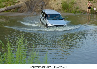 NOVOSIBIRSK - JULY 22: Car forces the river to the forest way. Flooded country road after heavy rains. July22, 2012 in Novosibirsk Russia