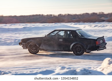 Novosibirsk, Russia - 02.02.2019: Old japanese car Nissan prepared for racing drive on the ice on a frozen lake, drifting and moving in a skidder in a turn on a specially cleared track