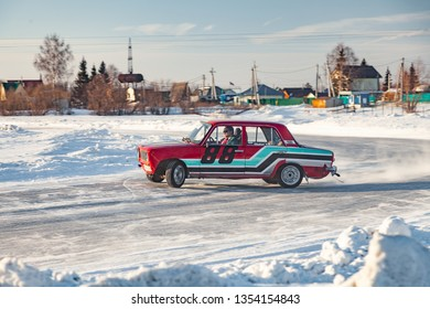 Novosibirsk, Russia - 02.02.2019: Old Russian cars Lada 2101 and 2104 prepared for racing drive on the ice on a frozen lake, drifting and moving in a skidder in a turn on a specially cleared track