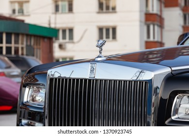 Novosibirsk, Russia - 04.11.2019: Front view of emblem Spirit of Ecstasy, grille and headlights of new a very expensive Rolls Royce Phantom car, a long black limousine, model outdoors on parking