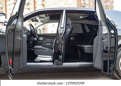 Novosibirsk, Russia - 04.11.2019: Interior view of new a very expensive Rolls Royce Phantom car, a long black limousine with opened doors, dashboard, steering wheel, seats on parking