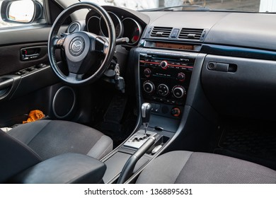 Novosibirsk, Russia - 04.12.2019: The interior of the car Mazda 3 with a view of the steering wheel, dashboard, seats and multimedia system with light gray trim and the letter-shaped emblem