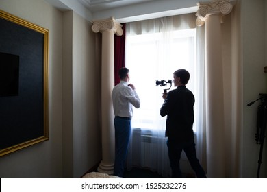 Novosibirsk, Russia - 06.15.2019: A videographer operator shoots a wedding video during the gathering and preparing the groom for a meeting with the bride in the room. Video camera with stabilization.