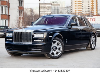 Novosibirsk, Russia - 07.25.2019: Front side view of new a very expensive luxury Rolls Royce Phantom car, a long black limousine, model outdoors, prepared for sale