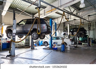 Novosibirsk, Russia - 08.01.2018: Three used cars with an open hood raised on a lift for repairing the chassis and engine in a vehicle repair shop. Auto service industry.