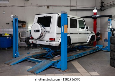 Novosibirsk, Russia - 08.01.2018: White used car Mercedes G-Class without wheels stands on the stand wheel alignment convergence of the car in the workshop for repair of vehicles Auto service industr
