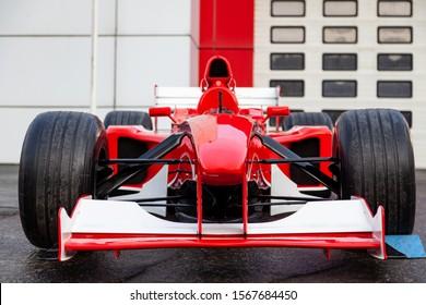 Novosibirsk, Russia - 11.01.2019: Red Ferrari racing sports cars for Formula 1 on the street near the garage box.