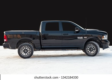 Novosibirsk, Russia - 12.01.2018: Black Dodge Ram with an engine of 5.7 liters side view on the background of black wall