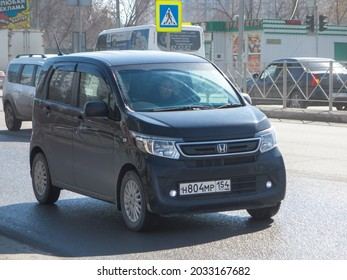 Novosibirsk, Russia - april 14 2021: private subcompact little black metallic japanese small basic key car new Honda N WGN, popular hatchback imported drive on winter sunny morning broad urban street