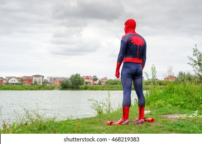 Novosibirsk, Russia - August 14, 2016: A man dressed as spider-man stands on the shore watching the town, close to dumbbells, after sports in Novosibirsk August 14, 2016.