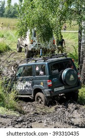 """Novosibirsk, Russia - August 16, 2014: SUV UAZ """"Patriot"""" pulls out of the puddle with dirt another machine for off-road competitions in Novosibirsk on August 16, 2014.  Soft focus."""