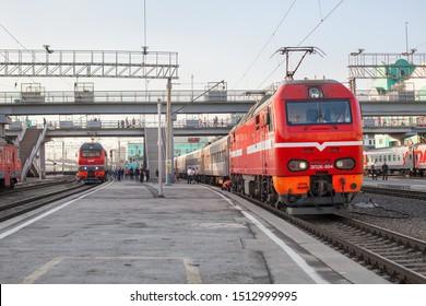 Novosibirsk, Russia - August 30, 2019: city railway station, passenger train wagons on platform close up, red electric locomotive on tracks, railroad transportation, modern rail road public carriage