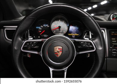 Novosibirsk, Russia – December 06, 2019:  Porsche Macan,  new car Interior - dashboard, player, steering wheel with logo and buttons, speedometer and tachometer