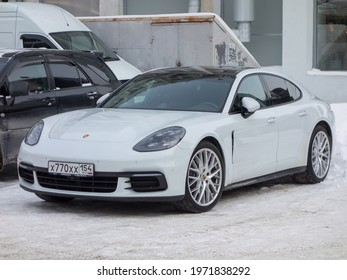 Novosibirsk, Russia - december 29 2020: private all-wheel drive white metallic color germany sport coupe 4-door Porsche Panamera 4 (971) luxury car awd 4wd 4x4 from Germany parking on winter street