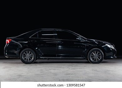 Novosibirsk, Russia - February 08, 2019:  Toyota Camry, side view. Photography of a modern car  on a parking in Novosibirsk against a black wall