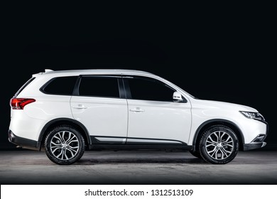 Novosibirsk, Russia - February 10, 2019:  Mitsubishi Outlander, side view. Photography of a modern car  on a parking in Novosibirsk against a black wall