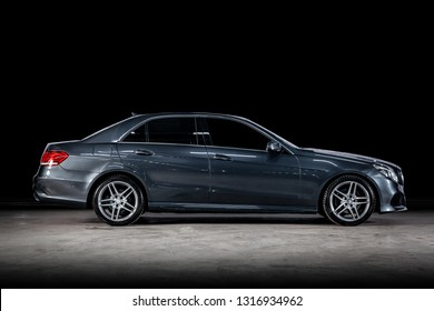 Novosibirsk, Russia - February 14, 2019:  Mercedes E-class , side view. Photography of a modern car  on a parking in Novosibirsk against a black wall