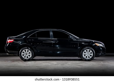 Novosibirsk, Russia - February 19, 2019:  Toyota Camry, side view. Photography of a modern car  on a parking in Novosibirsk against a black wall