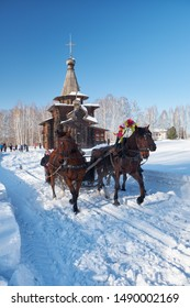 NOVOSIBIRSK, RUSSIA - JANUARY 11, 2018: Troika of horses harnessed to a sleigh.  Slavonic folk  winter festivities Shrovetide. The Church of the Savior. Historical Architectural Museum in the open air