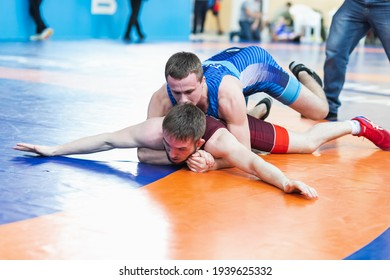 Novosibirsk, Russia – January  19, 2020 :   Russian Greco-Roman Wrestling Championship. Two young sportsmens wrestlers in red and blue uniform wrestling against wrestling carpet