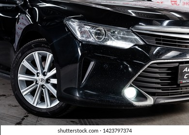Novosibirsk, Russia – June 11, 2019:  Toyota Camry,  close-up of the headlight, bumper, wheel. Photography of a modern car on a parking in Novosibirsk