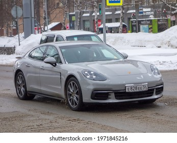 Novosibirsk, Russia - march 03 2021: private all-wheel drive gray metallic color germany sport coupe 4-door Porsche Panamera 4 (971) luxury car awd 4wd 4x4 from Germany driving on winter snow street