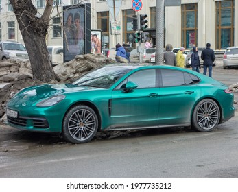 Novosibirsk, Russia - march 23 2021: private all-wheel drive green chrome metallic color germany sport coupe 4-door Porsche Panamera 4S (971) luxury car awd 4wd 4x4 parking on the dirty slush street