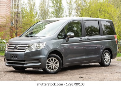 Novosibirsk/ Russia – May 02 2020: Honda Stepwgn,  front view of modern gray  minivan parked on green street  with summer  background.