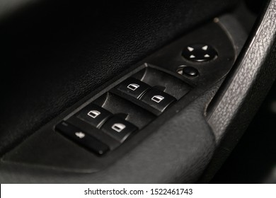 Novosibirsk, Russia – September 11, 2019:  BMW X1 , Close up of a door control panel in a new modern car. Arm rest with window control panel, door lock button, and mirror control.