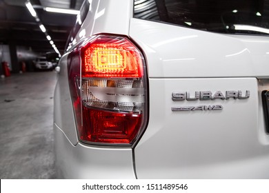 Novosibirsk, Russia – September 18, 2019:  close-up, the back of the car is a headlight, a bumper, a back cover of a baguette and an Subaru  nameplate on a plastic steering wheel. Car emblem Subaru