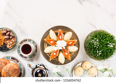 Novruz Azerbaijan traditional table setting, delicious sweet pastry on white background with tea cup, teapot, green wheat grass semeni. Golden plate of pakhlava and shekerbura and gogal, copy space