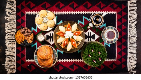Novruz Azerbaijan traditional table setting, delicious sweet pastry on folk rug background with tea cup, teapot, green wheat grass samani. Golden plate of pakhlava and shekerbura and gogal, copy space