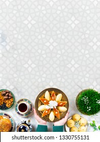 Novruz Azerbaijan traditional table setting, delicious sweet pastry on white oriental background with tea cup, teapot, green wheat grass semeni, plate of pakhlava and shekerbura and gogal, copy space
