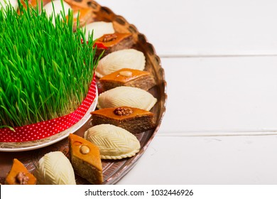 Novruz concept plate of traditional Azerbaijan pastries packlava and shekerbura in copper vintage tray with wheat grass semeni on white wooden table background, copy space for text